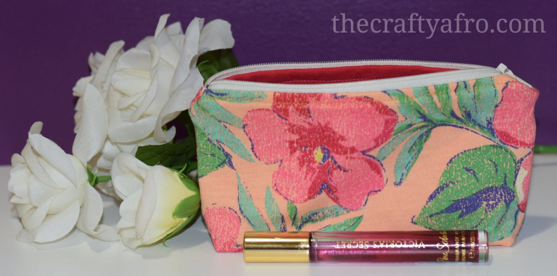 Flower themed zipper pouch in front of white roses.